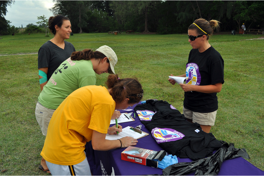 Jana Ritter talks to Gina Santoianni, Dana Henderson and Heather Hooper while they signed up for the Barefoot Wine Beach Cleanup Thursday, Sept. 8, at Ted Sperling Park.