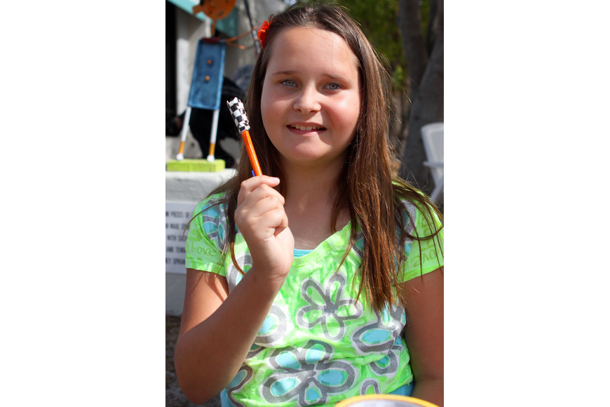 Destiny Parrish, 10, shows off one of her duck tape pen creations that she sold at the Siesta Key Craft Festival.