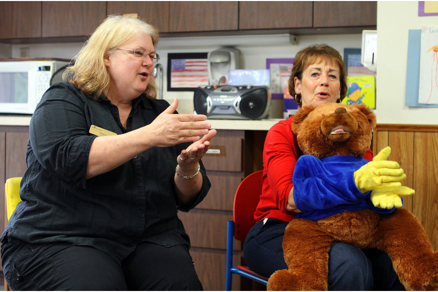 "Nancy Velazquez, Janice Frankel and BeeBo show the children, parents and caregivers the sign for ""cake""."
