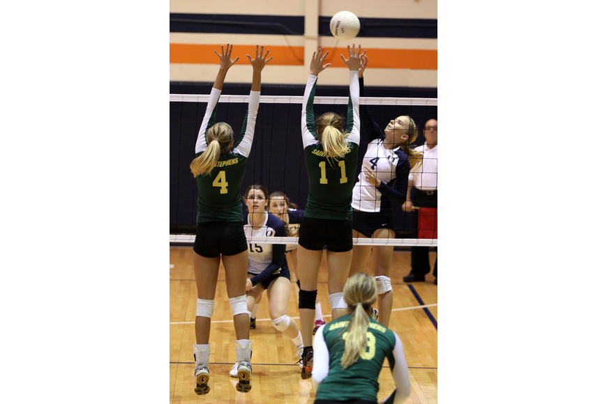 Natalie Buffett, No. 4, spikes the ball at Gabrielle Woodruff, No. 4, Amanda Everhardus, No. 11.