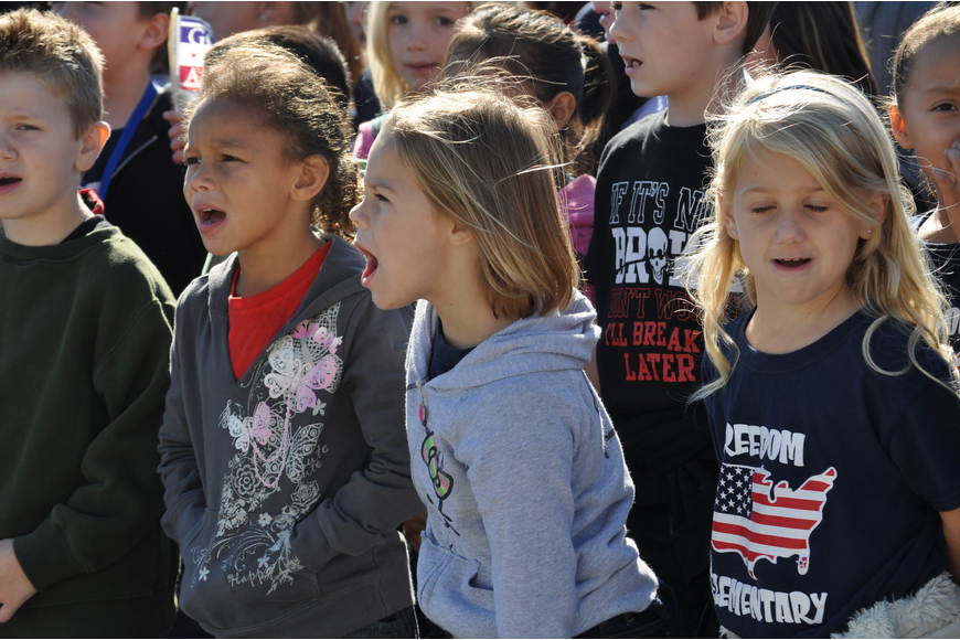 Children sang after the flag-raising ceremony at Freedom.