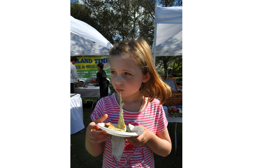 Maddie Cashen, 8, enjoys eating a piece of pizza from The Village Idiot Saturday, Nov. 17, at the Longboat Key Gourmet Lawn Party.