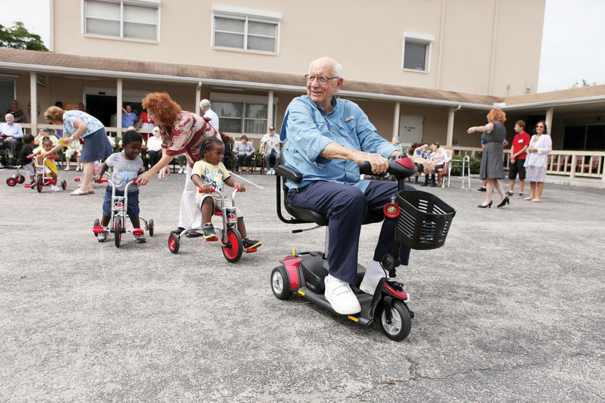 "Bob Ireland leads the toddlers on his scooter in a game of ""follow the leader,"" after the toddlers received brand new tricycles from the Rotary Club of Sarasota Bay."