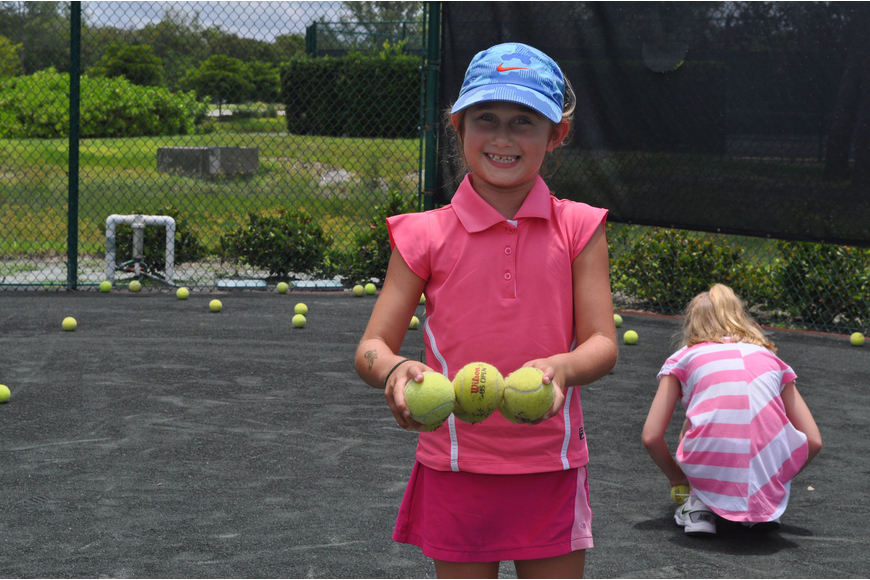 Clementine Schwartz picked up balls following drills at a July 23 tennis camp session at the Longboat Key Club and Resort Tennis Gardens.