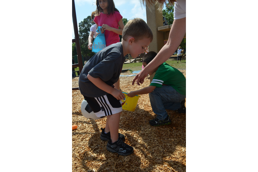Travis Neidert searches the playground for eggs.