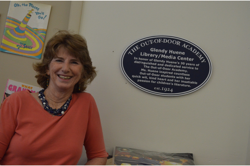 Glendy Huene stands in front of a plaque with her name inside the library.