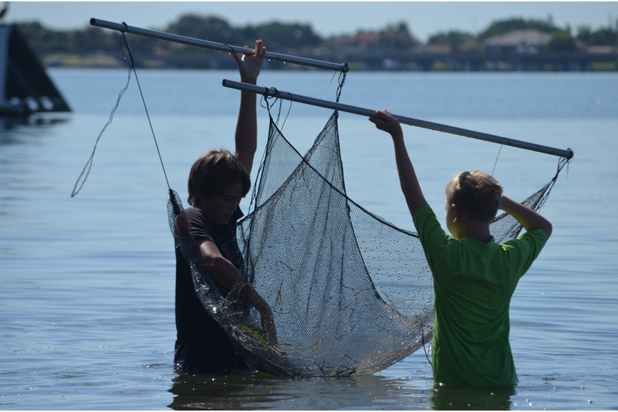 Jake Barrett, 12, and Ben Gansle, 10, lift up the trolling net to examine critters they catch.