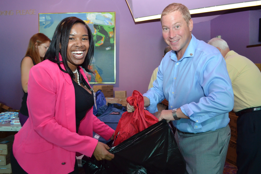 Theresa Carnegie hands James Ritcher a backpack filled with school supplies.