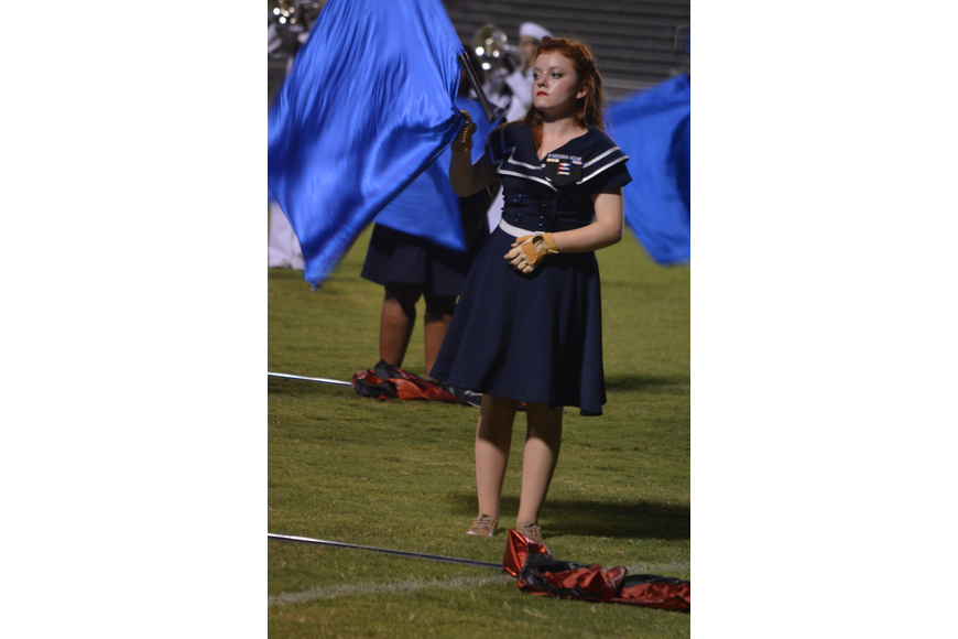 Sophomore Rose Marie Messina twirls a flag as part of the color guard during the halftime show.