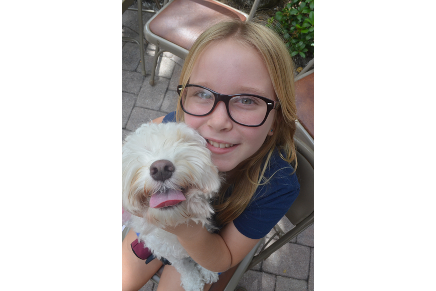 Caelin Gorman, 9, and her 2 – year old cockapoo Pretzel