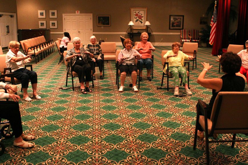 The chair dancers move their hands out and back for one of their exercise motions.