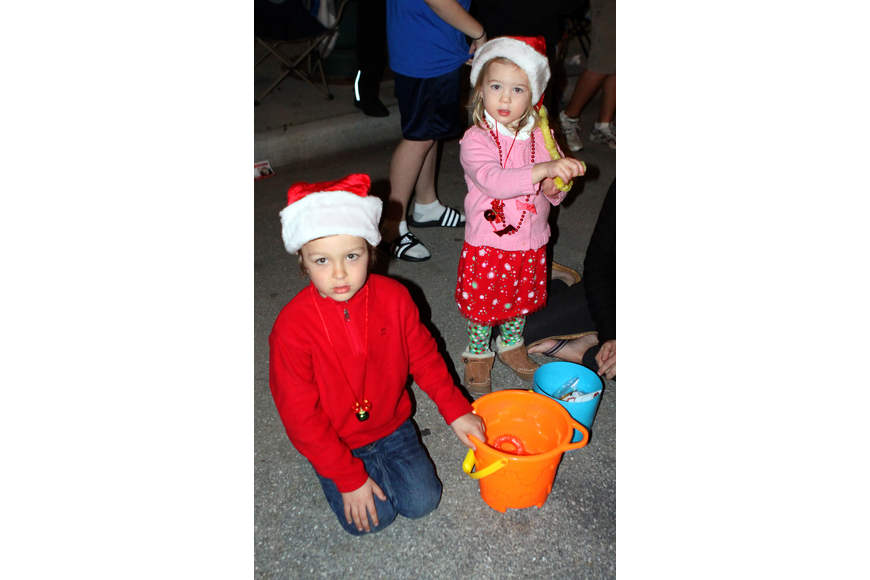 Kaleb and Mia Griffith collect tons of candy in their buckets during the parade.
