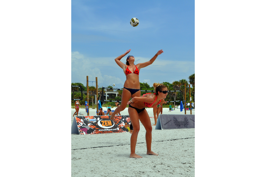 Livia Mendonca serves the ball while her teammate, Melissa Roberts, stays on her toes during their game against Kendra Van Zweiten and Shayna Munson in the Siesta Key Gulf Open, Saturday, July 9 at Siesta Key Beach.