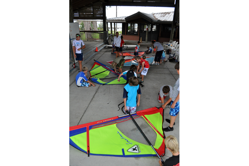 The campers try to disassemble their sails faster than the other groups Friday, July 8 during the Island Style Water Sports Camp.