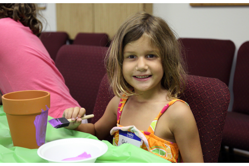 "Chloe Johnson, 6, paints her pot purple during craft time at ""Everglades Adventure"" vacation bible school."