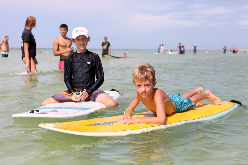 Ben Hershfeld, 11, hangs out on a surfboard next to his brother, Fisher, 7, Saturday, Sept. 15, during Hang 10 for Autism.