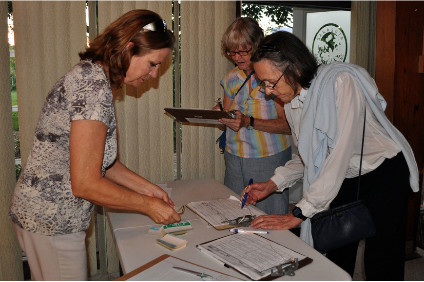 Dixie Stevens helps Freddie WindRiver and Nancy Aldrich sign in for the meeting and talk Thursday, Oct. 11, at the Sarasota Garden Club.