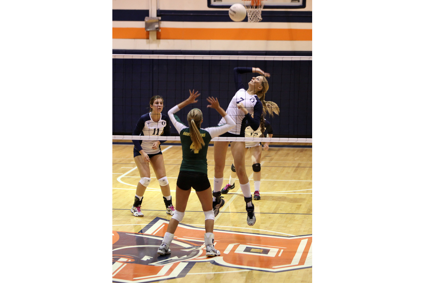 Emily Greenwood, No. 7, prepares to hit the ball while Gabrielle Woodruff, No. 4, gets in position to block.