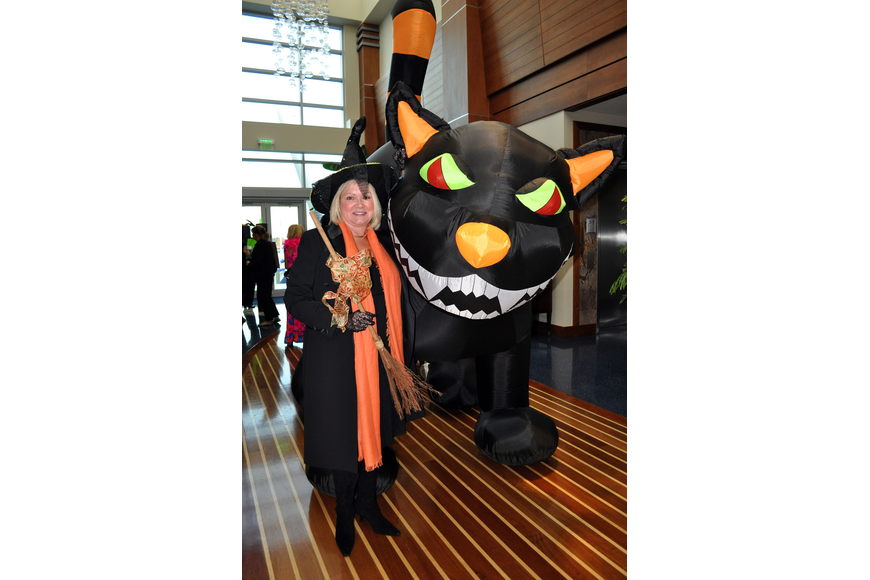 Kathleen Garcia dressed as a witch and posed next to the inflatable, moving, black cat.