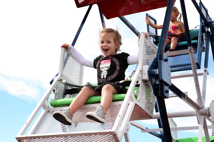 Rylan Meredith, 3, laughs and smiles at her family as she rides the Ferris wheel Saturday, Oct. 27.