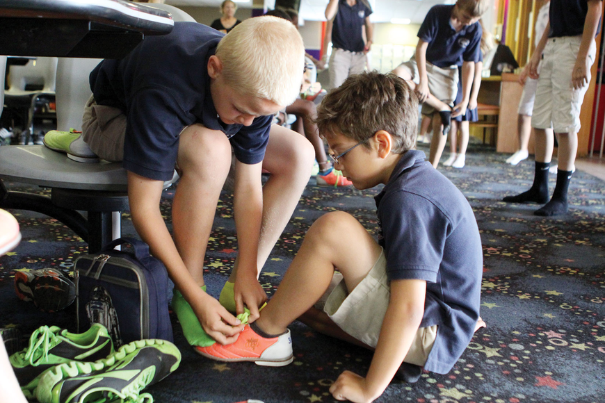 Sixth grader Taber Chadwick, 12, helps his buddy, first grader Pedro Princeno, 7 May 17, at Sarasota Lanes.