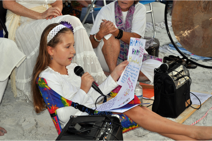 Ella Mirman reads a prayer for the world that she wrote herself to the crowd during the ceremony.