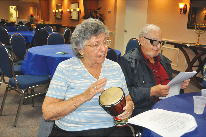 Renee Gold plays one of the many drums and sings along with her husband, Bert, at Temple Emanu-El's La La La Havdalah event.