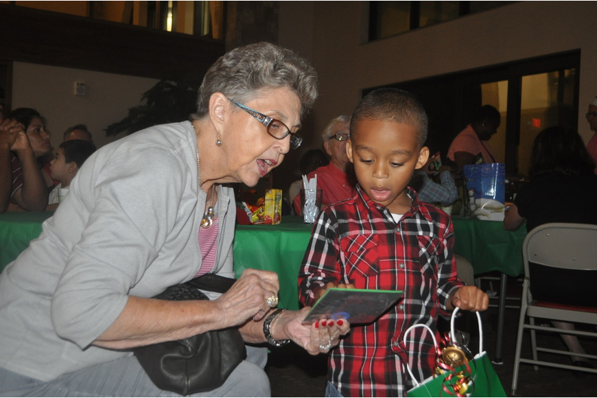 Cassan Johnson, 3, shows reading buddy Jane Anderson the tic tac toe book he received from Santa.