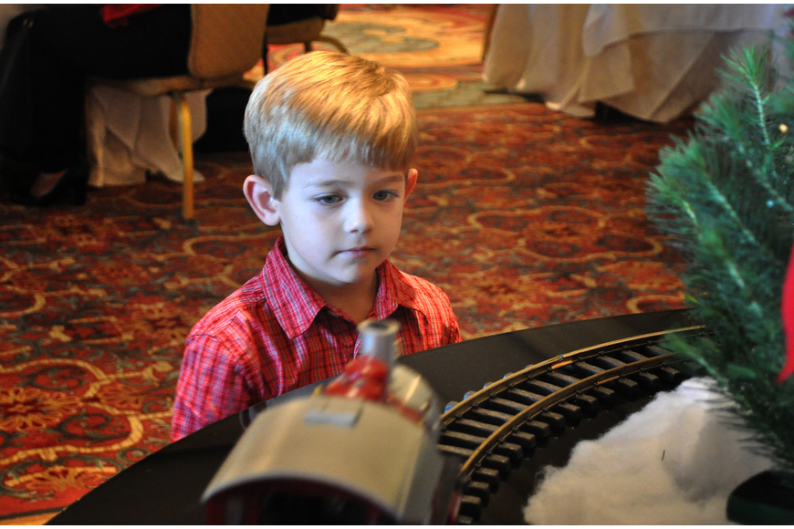 Tyler McCoy, 4, watches the electric, toy train make its way around the track.