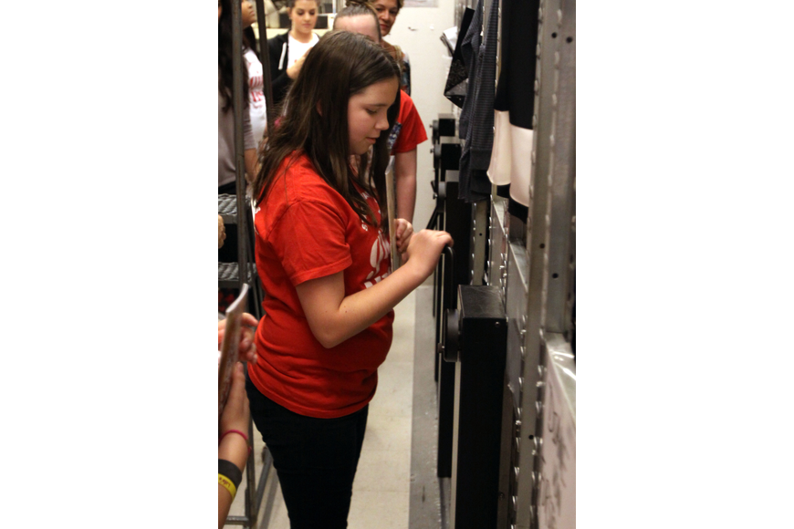 Mikayla Klauber has a chance to move the moveable shelving units in one of the back rooms of the store.