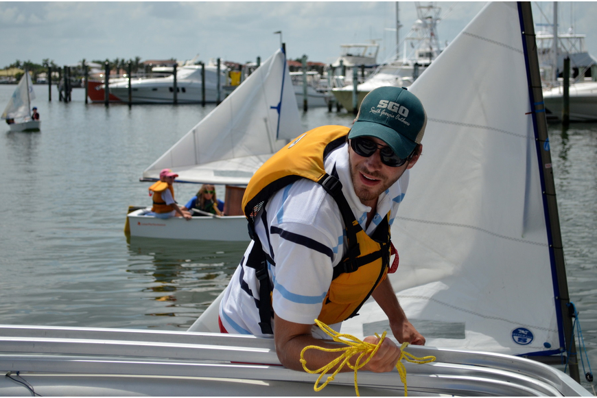 Sailing instructor Joseph Strickland pulls the campers to the dock.