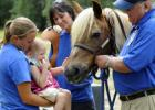 Two-and-one-half-year-old Izzy Dean, pictured with SMART's Alissa Fabian, Heidi Conover and Dennis Lewis, loved getting to pet the horse.